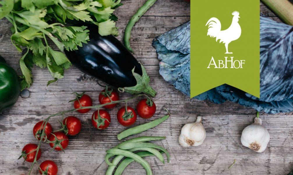 Die Marke Abhof die von einem weißen Hahn auf grünen Hintergrund dargestellt wird mit Gemüse auf einem Holztisch im Hintergrund