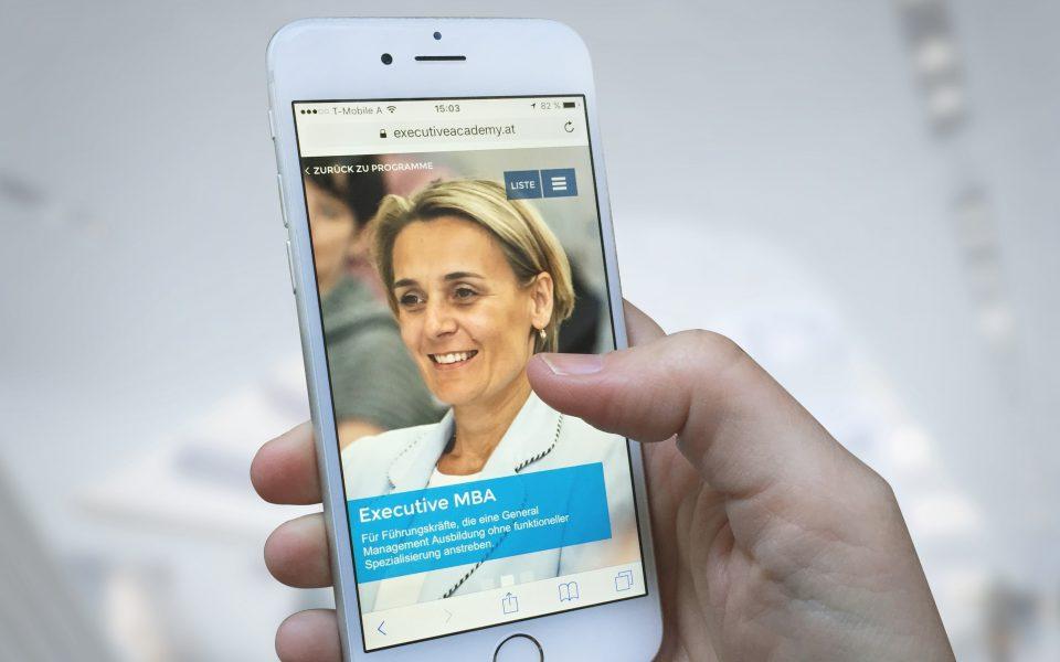 Eine Dame von der WU Executive Academy auf einem Smartphone