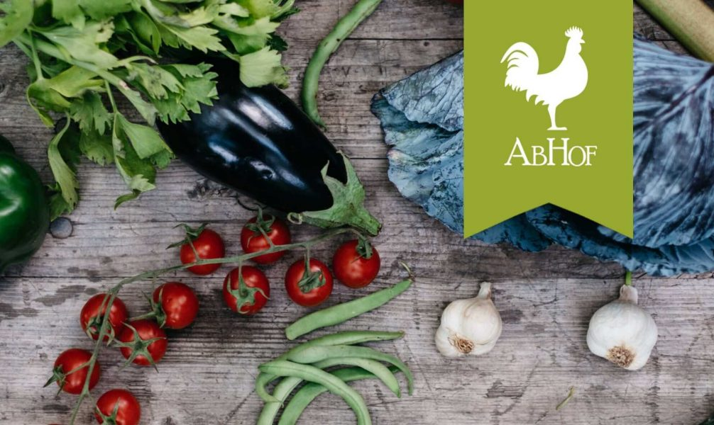 The brand Abhof which is represented by a white rooster on green background with vegetables on a wooden table in the background